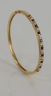 14 karat gold bangle bracelet, set with nine diamonds and ten sapphires.  14.4 grams