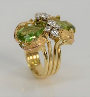 18 karat gold ring, set with two pear shaped green peridot, 6.5 cts. and elegant round brilliant cut diamonds. size 7, 16.2 grams to...