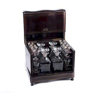 Caja licorera. Francia, siglo XIX. Estilo Napoleón III. Elaborada en madera de palisandro con aplicaciones de latón. Piezas: 21