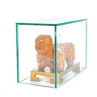 Almohadilla*. China, siglo XVIII/XIX. Talla en madera. Con base de bronce y capelo de vidrio. Diseño a manera de personaje reclinado.
