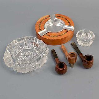 Lote mixto de 6 piezas SXX. Elaborados en cristal y madera tallada. Con aplicaciones de metal plateado. Consta de 3 ceniceros y 3 pipas