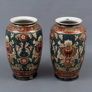 Par de jarrones. China. Siglo XX. Elaborados en porcelana. Decorados con elementos orgánicos. florales y vegetales a mano.