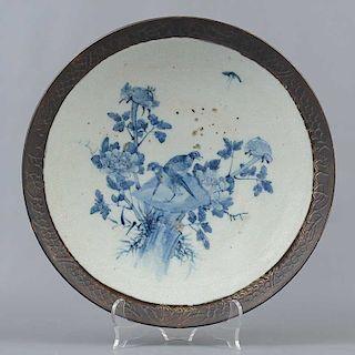 Plato decorativo. Origen oriental. Elaborado en ceramica. Acabado brillante. Decorado con elementos vegetales, florales y zoomorfos.