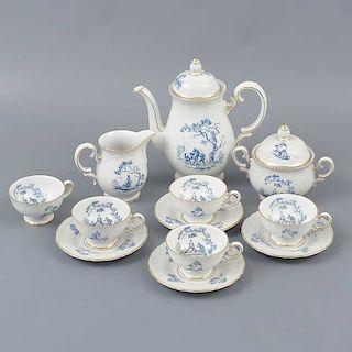 Juego de té. Alemania. Siglo XX. Elaborado en porcelana de Bavaria. Decorado con esmalte dorado, escena campirana, elementos...