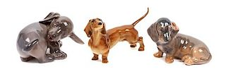 * A Group of Three Dachshund Porcelain Figures Width of widest 5 1/8 inches.