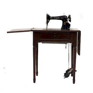 Máquina de coser. Estados Unidos, siglo XX. Marca Singer. En talla de madera tallada y enchapada. Con cubierta rectangular abatible.