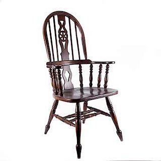"Sillón. Siglo XX. Estilo Early American. Elaborado en madera tallada. Respaldo con barandillas, asiento liso y chambrana en ""H""."
