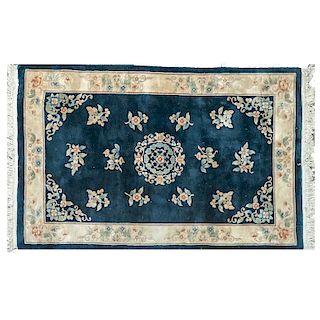Tapete. China, siglo XX. Estilo Abusson. Elaborado en fibras sintéticas. Decorado con motivos florales sobre fondo azul.
