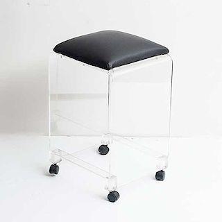Banco. Años 60. Estructura de acrilico transparente. Con asiento acojinado de piel color negro y ruedas inferiores.