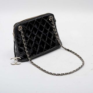 Bolso para dama. Francia, siglo XX. De la firma Chanel. Diseño clásico de la firma color negro, con interior en piel color rojo.
