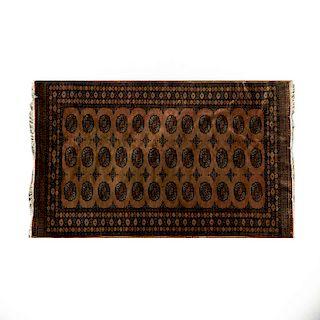 Tapete. Pakistán, siglo XX. Elaborado en fibras de lana y algodón. Decorado con motivos geométricos sobre fondo café.