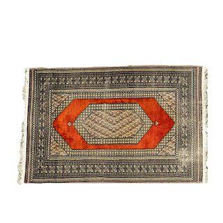 Tapete. Siglo XX. Estilo Bokahara. Elaborado en fibras de lana y algodón. Decorado con motivos geométricos y medallón central.