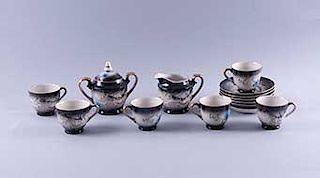 Servicio abierto de té Japón,S. XX.Elaborada en semi porcelana tipo tsatsuma, color negro.Decorados con dragones en alto relieve.Pzs:14