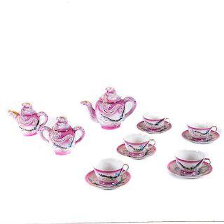 Servicio de té. Japón, siglo XX. Elaborado en porcelana tipo tsatuma color rosa. tetera, cremera, azucarera. Piezas: 18