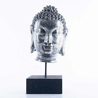 Rostro de Siddhartha. Siglo XX. Elaborado en resina esmaltada color plateado. Con base de madera.