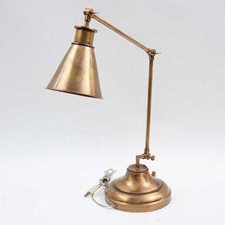 Lámpara de escritorio. Siglo XX. Elaborada en latón. Para 1 luz. Con pantalla cónica, brazos moviles y base circular escalonada.