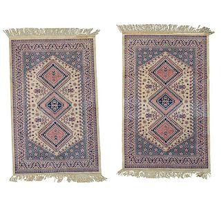 Par de tapetes. Pakistán, siglo XX. Elaborados en fibras de lana y algodón. Decorados con motivos geométricos sobre fondo rosa.Pzs: 2