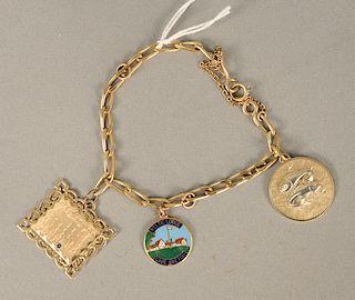 14 karat gold bracelet with two 14 karat and one 10 karat gold charm. 20.9 grams total weight