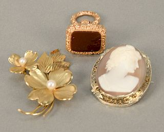 Three piece lot to include 14 karat gold floral pin, 14 karat white gold set with cameo, and a watch fob. 9.8 weighable grams plus p...