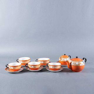 Servicio de té. Japón, siglo XX. Elaborados en porcelana color naranja acabado brillante. Decorado con motivos florales. Pzs: 13
