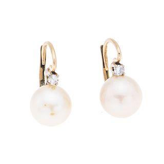 Par de aretes con perlas en oro amarillo de 10k y metal base dorado. 2 perlas color crema de 10mm. 2 acentos de diamantes. Pes...