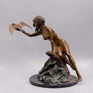 Escultura de mujer con ave. Siglo XX. Fundición en bronce patinado sobre base circular de mármol negro.