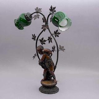 Lámpara de mesa. Siglo XX. Elaborada en antimonio patinado con fuste a manera de niño recolector con pantallas de vidrio.
