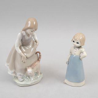Niña con gato y niña con flor. España, siglo XX. Elaboradas en porcelana acabado brillante, una Lladró. Piezas: 2
