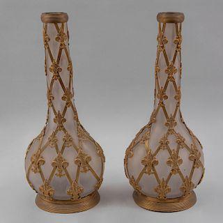 Par de floreros. Origen europeo, siglo XX. Elaborados en cristal opaco con aplicaciones de metal dorado. Piezas: 2.