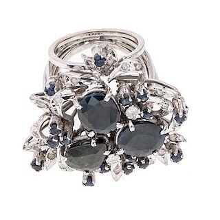 Anillo con zafiros y diamantes en plata paladio. 18 zafiros corte oval y redondo. 20 acentos de diamantes. Talla: 5. Peso: 1...