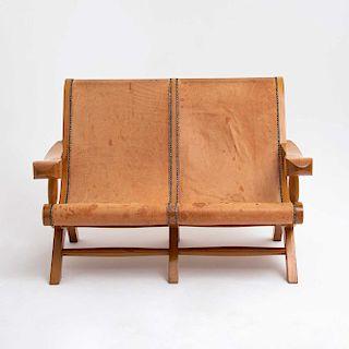 Love seat. México, siglo XX. Estilo Miguelito. Elaborado en madera. Diseño curvo. Con respaldo y asiento en tapicería de cuero café.