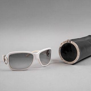 Gafas de sol. De la marca Bvlgari. Armazón de acetato blanco con micas en oscuro desvanecido. Con estuche de la marca.