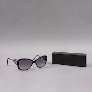 Gafas de sol. De la marca Tiffany. Armazón de acetato con terminales metálicas con micas en oscuro desvanecido. Con estuche.