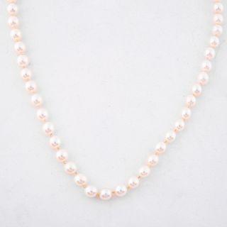 Collar con 65 perlas cultivadas color crema de 8 mm. Broche con 9 rubíes corte redondo. Peso: 54.2 g.