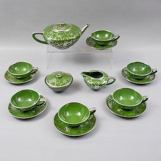 Juego de té. Siglo XX. Elaborado en porcelana verde acabado brillante con cenefa orgánica y filos en esmalte de plata. Pz:15