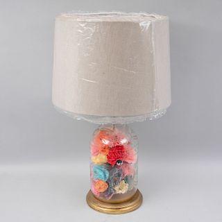 Lámpara de mesa. México, siglo XX. Fuste de botellón de vidrio con esgrafiados florales, base de madera y pantalla arpillada.