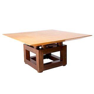 Mesa. Siglo XX. Elaborada en madera tallada. Cubierta cuadrangular con recubrimiento ajedrezado de pergamino y pedestal cudrangular.
