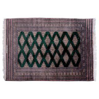 Tapete. Pakistán, siglo XX. Estilo Bokhara. Elaborado en fibras de lana, algodón y ensedado. Decorado con motivos geométricos.