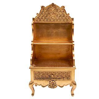 Aparador. Siglo XX. Elaborado en madera tallada dorada. Con 2 repisas, cajón con tirador tipo perilla y soportes curvos.