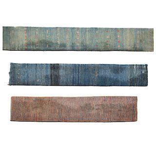 Lote de 3 tapetes. SXX. Diferentes diseños. En fibras de lana y algodón. Decorados con elementos geométricos y rayados. 425 x 105 cm.