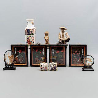 Lote mixto de 16 piezas. Diferentes orígenes, materiales y diseños. SXX. Consta de: jarrón, elefante, 2 capelos, portaretrato, otros.