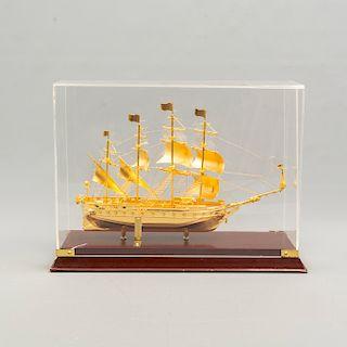 Galeón. México. Siglo XX. Diseño a escala. Elaborado en metal dorado. Hutchison Ports México. Con base y capelo. 28 x 39 x 14 cm.