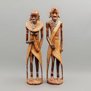 Pareja de ídolos africanos. Siglo XX. En madera policromada. Decorados con joyería elaborada con chaquiras y cuentas. 63 x 15 x 9 cm.
