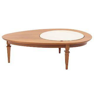 Mesa de centro. SXX. En talla de madera. Con cubierta oval de piel y madera, fustes arquitectónicos. 35 x 120 x 70 cm.