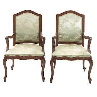 Par de sillones. Siglo XX. En talla de madera. Con respaldos cerrados y asientos en tapicería floral verde.