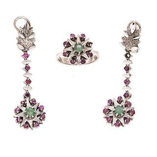 Anillo y par de aretes con esmeraldas y rubíes en plata paladio. 3 esmeraldas corte redondo. 31 rubíes corte redondo. Talla: 5 1/2.