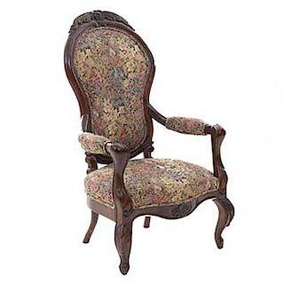 Sillón. Siglo XX. Estilo Victoriano. En talla de madera. Con respaldo cerrado y asiento en tapicería floral.
