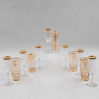 Servicio de vasos y copas. Siglo XX. Elaboradas en vidrio transparente con cenefa y anillados de esmalte dorado. Piezas: 12