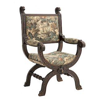 Sillón-curul. Francia. Siglo XX. En talla de madera de roble. Tapicería de tela con diseño floral. Con respaldo semiabierto.