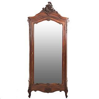 Armario. Francia. Siglo XX. Estilo Luis XV. En talla de madera de roble. Con puerta con espejo de luna biselada. 252 x 133 x 53 cm.
